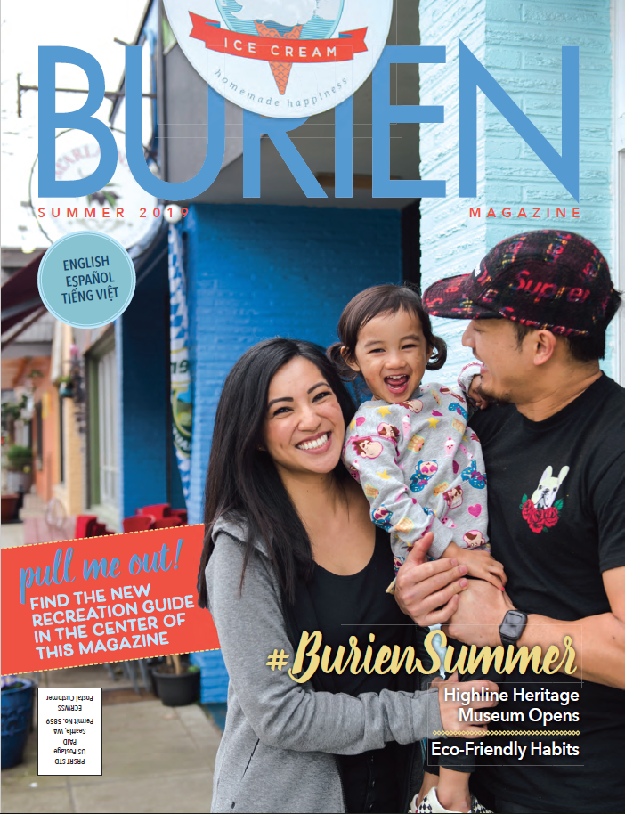 Magazine cover. Parents hold child in front of shop.