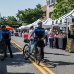 Police officer, bicycle and farmers market.
