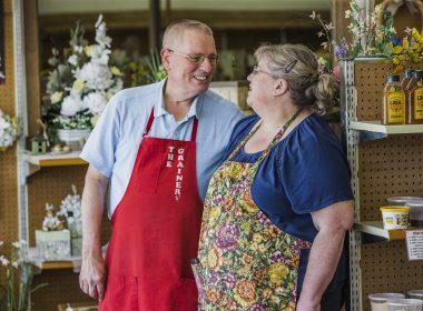 Two people wearing aprons look at each other.