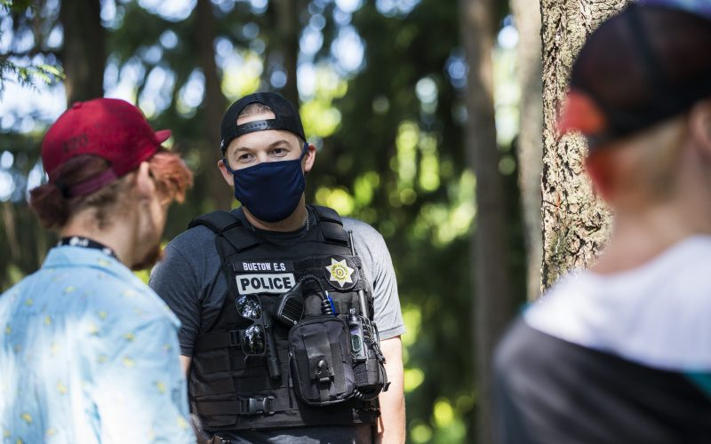 Burien Police Officer speaks to a person in a park.