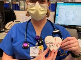 Health care worker in PPE holds heart shaped cookie.