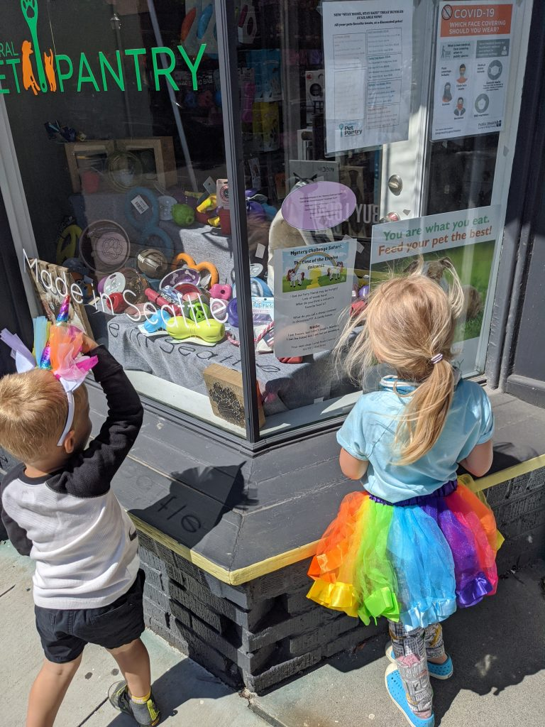 Children in rainbow costumes looking at store window.