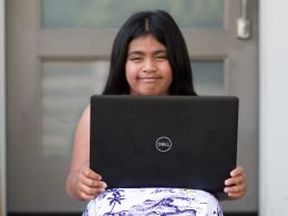 Child holds laptop.