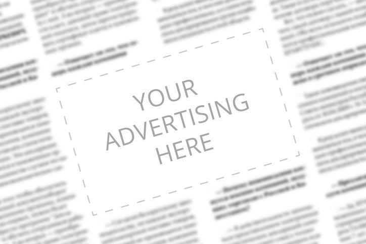 Close up of a copy space with wrtitten words Your Advertising Here on a blurred background of a newspaper. Business concept. Adding ad into paper page. Mockup of a newspaper advertisement column