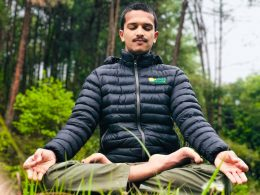 Man in lotus position with eyes closed.