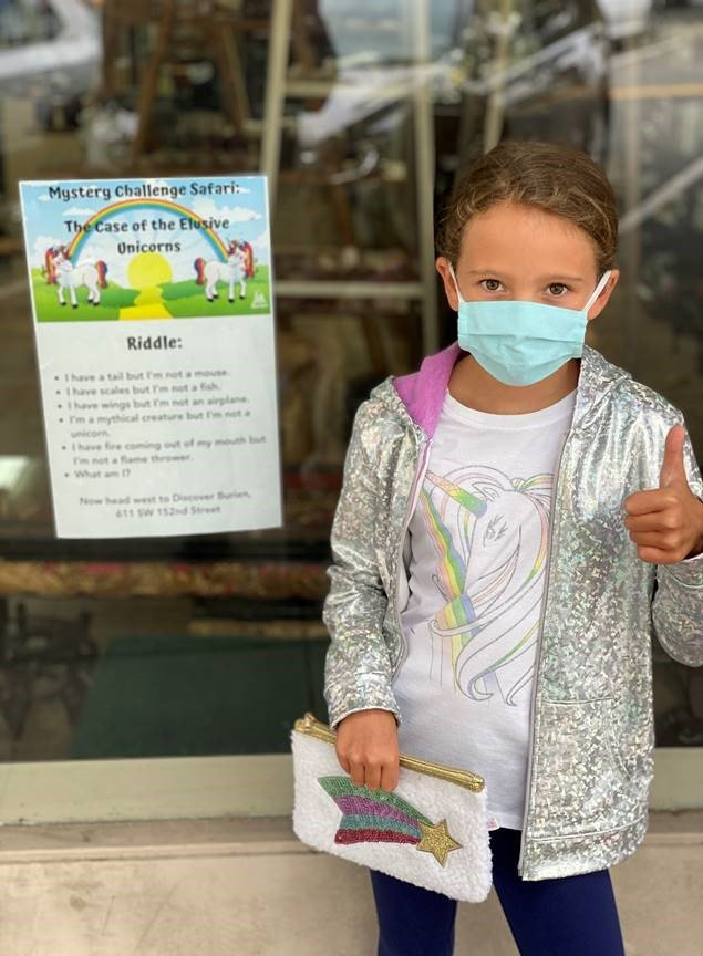 Girl in mask next to Unicorn Challenge sign with thumbs up.