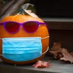 Pumpkin with sunglasses and cloth face mask outdoors on front porch steps surrounded by fall leaves.