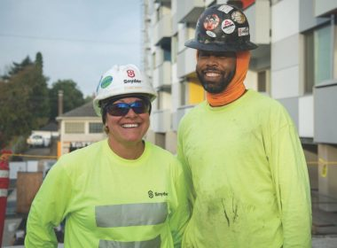 Two people in wearing hard hats and safety gear.