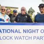 Adults standing in front of National Night Out Block Watch Party banner.