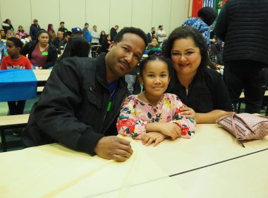 Two adults and child at table.