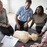 Adults kneeling around a CPR training dummy.