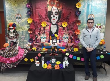 Man stands next to Day of the Dead altar.