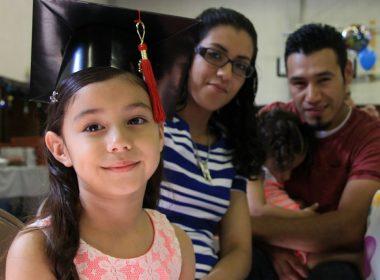 Child wearing graduation cap and parents.