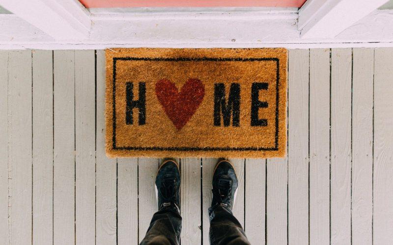 Feet in front of doormat with word home.