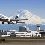 Airplane taking off runway, Mt. Rainier in background.