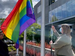 Two people raise Pride banner on flagpole.