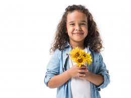 Child holding yellow flowers.