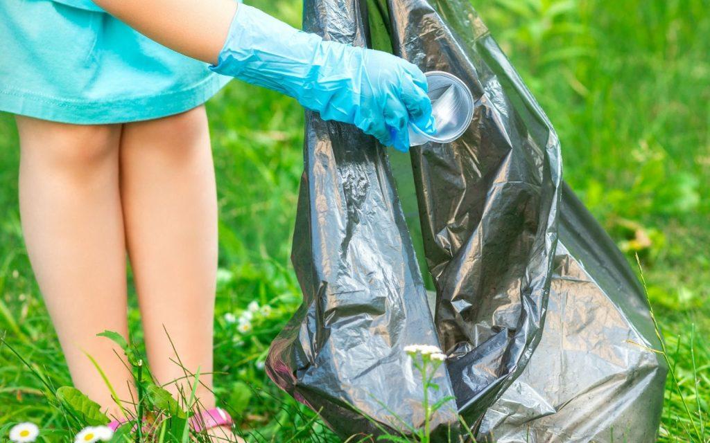 Child wearing gloves picking up trash and holding trash bag.