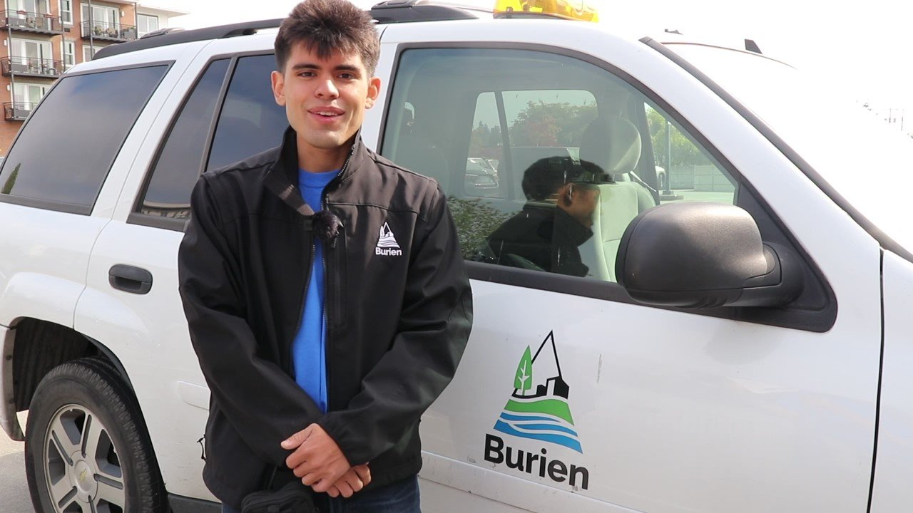 Person stands in front of Burien vehicle.